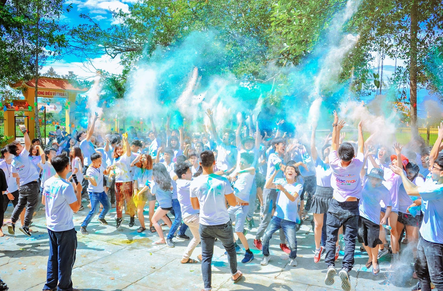 people throwing blue powder at daytime